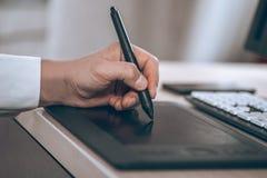 Espace de travail du ` s de concepteur Main sur le comprimé de stylo Jeune homme futé dans le bureau L'espace noir gratuit de cop Photos stock