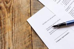 Espace de travail en bois avec le document et stylo pour le signe pour la vue supérieure de jour d'homme d'affaires Images stock