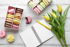 Espace de travail féminin avec des macarons et des tulipes Photographie stock