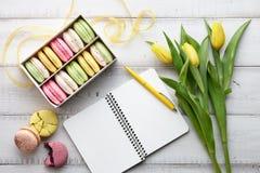 Espace de travail féminin avec des macarons et des tulipes Images libres de droits