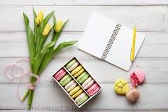 Espace de travail féminin avec des macarons et des tulipes Photos stock