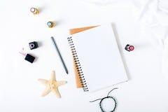 Espace de travail féminin avec le bloc-notes, le crayon, le bracelet et le clou ouverts Image libre de droits