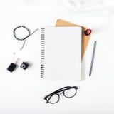Espace de travail féminin avec le bloc-notes, crayon, rouge à lèvres, lunettes, b Photographie stock