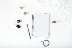 Espace de travail féminin avec le bloc-notes, le crayon, le bracelet et le clou ouverts Photos libres de droits
