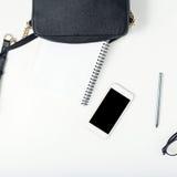 Espace de travail féminin avec le sac en cuir noir, smartphone, bloc-notes, Photo libre de droits