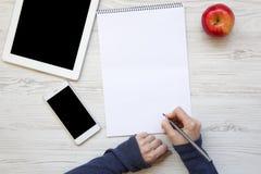 Espace de travail féminin avec le smartphone, le comprimé, le carnet et la pomme Photographie stock libre de droits