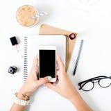 Espace de travail féminin avec le smartphone dans des mains femelles Configuration plate Images libres de droits