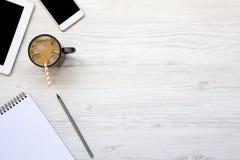Espace de travail féminin avec le smartphone, la glace de latte, le comprimé et le notebo Photos libres de droits