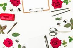 Espace de travail féminin de bureau avec le presse-papiers, le carnet, les accessoires et les fleurs rouges sur le fond blanc Con Photos stock