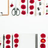 Espace de travail féminin de bureau de Blogger ou d'indépendant avec le presse-papiers, le carnet, les fleurs rouges et les acces Photo libre de droits