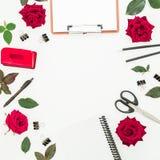 Espace de travail féminin de bureau de Blogger ou d'indépendant avec le presse-papiers, le carnet, les roses rouges et les access Images libres de droits