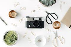 Espace de travail féminin de bureau avec l'appareil-photo succulent et rétro, les ciseaux, le journal intime et les agrafes d'or  Image stock