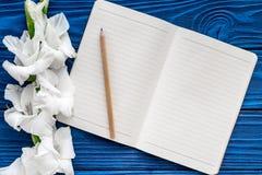 Espace de travail féminin de bureau Carnet et glaïeul sur la maquette en bois bleue de vue supérieure de fond Photo libre de droits