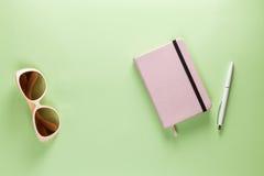 Espace de travail féminin moderne d'indépendant Tableau plat de Pistache de configuration avec le journal intime rose-clair, styl Images stock