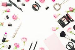 Espace de travail femelle avec des cosmétiques, les accessoires et les roses roses sur le fond blanc Vue supérieure Configuration Images stock