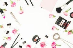 Espace de travail femelle avec des cosmétiques, les accessoires et les roses roses sur le fond blanc Vue supérieure Configuration Photos stock
