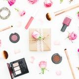 Espace de travail femelle avec des cosmétiques, les accessoires et les roses roses sur le fond blanc Vue supérieure Configuration Photographie stock