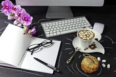 Espace de travail femelle avec l'ordinateur, l'orchidée, le café et le carnet avec des verres et le stylo sur le fond noir Photographie stock libre de droits