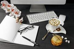 Espace de travail femelle avec l'ordinateur, l'orchidée, le café et le carnet avec des verres et le stylo sur le fond noir Images libres de droits