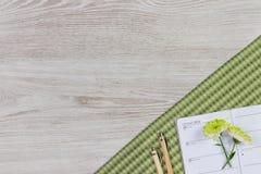 Espace de travail femelle avec la fleur, les accessoires, le stylo, le crayon et le journal intime Images stock