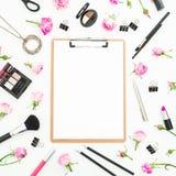 Espace de travail de femme avec des cosmétiques presse-papiers, accessoires et roses roses sur le fond blanc Vue supérieure Confi Images stock