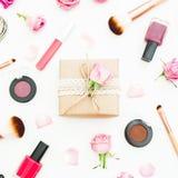 Espace de travail de femme avec le boîte-cadeau, roses roses, cosmétiques, journal intime sur le fond blanc Vue supérieure Config Photographie stock libre de droits