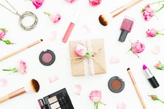 Espace de travail de femme avec le boîte-cadeau, roses roses, cosmétiques, journal intime sur le fond blanc Vue supérieure Config Images libres de droits