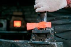 Espace de travail de forgeron Forgeron travaillant avec le métal d'un rouge ardent du nouveau marteau à l'enclume dans une forge  image stock