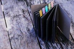 Espace de travail minimal : le carnet avec des couleurs notent l'étiquette sur vieil en bois Images stock