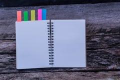 Espace de travail minimal : le carnet avec des couleurs notent l'étiquette sur vieil en bois Photos stock