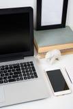 Espace de travail moderne avec la maquette d'ordinateur portable sur une table Images libres de droits