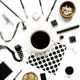 Espace de travail noir de style avec du café noir, carnet à dessins, serviettes, rubans, pinceaux sur le fond blanc Images libres de droits