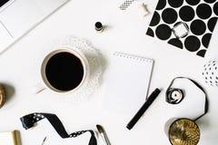 Espace de travail noir de style d'indépendant avec du café noir, carnet à dessins, serviettes, rubans, pinceaux Images stock