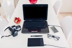 Espace de travail de photographe d'indépendant dans la cuisine Travaillant de la maison utilisant le comprimé d'ordinateur portab Photo stock
