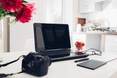 Espace de travail de photographe d'indépendant dans la cuisine Travaillant de la maison utilisant le comprimé d'ordinateur portab Photographie stock libre de droits