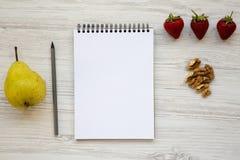 Espace de travail pour la personne en bonne santé : bloc-notes, crayon, noix, fraises et poire vides sur un fond en bois blanc Photographie stock libre de droits