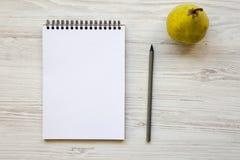 Espace de travail pour la personne en bonne santé : carnet, crayon et poire sur un fond en bois blanc Photos libres de droits