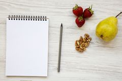Espace de travail pour la personne en bonne santé : carnet, crayon, noix, fraises et poire sur un fond en bois blanc Image stock