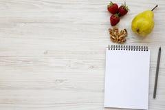 Espace de travail pour la personne en bonne santé : carnet, crayon, noix, fraises et poire sur un fond en bois blanc D'en haut, c Images libres de droits