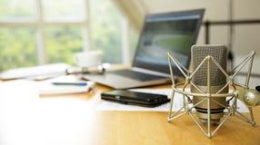 Espace de travail pour le journalisme avec le microphone de condensateur, ordinateur portable, cellule Photographie stock libre de droits