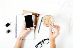 Espace de travail de siège social avec le smartphone dans des mains femelles Configuration plate Photographie stock