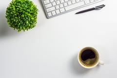 Espace de travail sur la table avec le clavier d'ordinateur, le stylo, la tasse de café et le pot d'usine images libres de droits