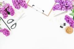 Espace de travail sur le fond blanc avec le presse-papiers, le carnet, les ciseaux, le lilas et les accessoires Configuration pla Image libre de droits