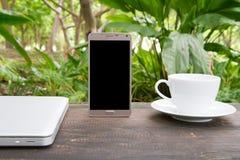 Espace de travail vert conceptuel, ordinateur portable avec l'écran vide sur la table, tasse de café et fond vert de jardin, conc Images libres de droits