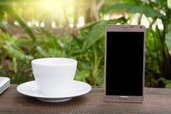 Espace de travail vert, mobiles conceptuels avec l'écran vide sur la table, la tasse de café et le fond vert de jardin, conce de  Photographie stock