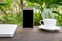 Espace de travail vert, mobiles conceptuels avec l'écran vide sur la table, la tasse de café et le fond vert de jardin, conce de  Image libre de droits