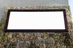 Espace publicitaire dans le cadre en bois sur le mur en pierre, OIN vide de blanc Photos libres de droits