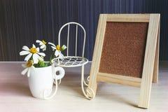 Espace vide dans le petit conseil avec la chaise de fleur et de vintage Image stock