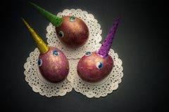 Espacez les oeufs colorés de licornes avec des yeux sur le fond noir Pâques Photographie stock libre de droits