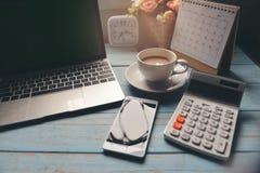 Espacio de funcionamiento en casa Escritorio de oficina con la taza de café, de ordenador portátil de escritorio, del calendario  fotos de archivo libres de regalías